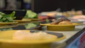 Μεταφορέας τροφίμων Ασιατικός καφές ύφους με τα τρόφιμα που κινούν σε έναν μεταφορέα τα μικρά πιάτα Έννοια της σπατάλης τροφίμων  φιλμ μικρού μήκους