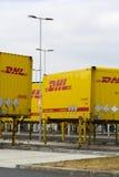 Μεταφορικά κιβώτια DHL μπροστά από τις διοικητικές μέριμνες του Αμαζονίου που χτίζουν στις 12 Μαρτίου 2017 μέσα Dobroviz, Τσεχία Στοκ Φωτογραφία