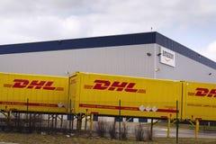 Μεταφορικά κιβώτια DHL μπροστά από τις διοικητικές μέριμνες του Αμαζονίου που χτίζουν στις 12 Μαρτίου 2017 μέσα Dobroviz, Τσεχία Στοκ Εικόνα