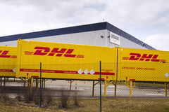 Μεταφορικά κιβώτια DHL μπροστά από τις διοικητικές μέριμνες του Αμαζονίου που χτίζουν στις 12 Μαρτίου 2017 μέσα Dobroviz, Τσεχία Στοκ Εικόνες