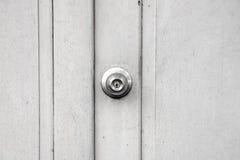 Μεταλλικό εξόγκωμα στην άσπρη ξύλινη πόρτα, ανοξείδωτο γύρω από το εξόγκωμα πορτών σφαιρών Στοκ φωτογραφία με δικαίωμα ελεύθερης χρήσης