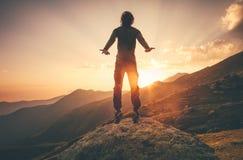 Μετεωρισμός πετάγματος νεαρών άνδρων που πηδά στα βουνά ηλιοβασιλέματος Στοκ Φωτογραφίες