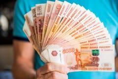Μετονομασίες πέντε χιλιάες ρωσικών ρουβλιών Δέσμη των τραπεζογραμματίων που απομονώνονται στο αρσενικό χέρι 5000 ρούβλια μετρητά  στοκ φωτογραφία με δικαίωμα ελεύθερης χρήσης