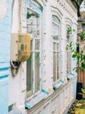 Μετρητής ηλεκτρικής ενέργειας στο κτήριο Παλαιό ασπρισμένο σπίτι Στοκ Φωτογραφίες