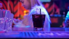 Μετρητής φραγμών στη σκοτεινή κινηματογράφηση σε πρώτο πλάνο δωματίων του γυαλιού με το λαμπιρίζοντας μαύρο ποτό με το strawÑŽ απόθεμα βίντεο