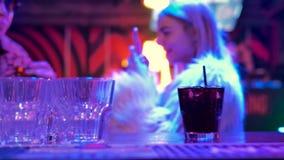 Μετρητής φραγμών στη σκοτεινή κινηματογράφηση σε πρώτο πλάνο δωματίων του γυαλιού με το λαμπιρίζοντας μαύρο ποτό με το άχυρο φιλμ μικρού μήκους