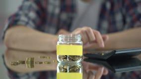 Μετρώντας δαπάνες ατόμων, που βάζουν τα χρήματα στο βάζο γυαλιού με την κενή αυτοκόλλητη ετικέττα για τη σημείωση φιλμ μικρού μήκους