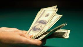 Μετρώντας μετρητά δολαρίων προσώπων, τυχερός λαχειοφόρος αγορά ή νικητής χαρτοπαικτικών λεσχών, εθισμός παιχνιδιού απόθεμα βίντεο