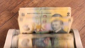 Μετρώντας ρουμανικούς πενήντα λογαριασμούς lei με την αντίθετη μηχανή - τοπ άποψη απόθεμα βίντεο