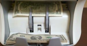 Μετρώντας τραπεζογραμμάτια αμερικανικών δολαρίων στην αντίθετη μηχανή νομίσματος φιλμ μικρού μήκους
