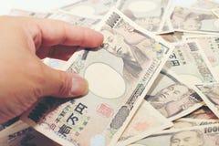 Μετρώντας χρήματα χεριών, ιαπωνική σημείωση νομίσματος, ιαπωνικά γεν στο άσπρο υπόβαθρο Στοκ Εικόνα