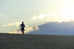 Μετωπική σκιαγραφία του νεαρού άνδρα που τρέχει στην κατάρτιση επαρχίας στο θερινό ηλιοβασίλεμα Στοκ εικόνες με δικαίωμα ελεύθερης χρήσης