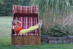Με ένα δροσερό ποτό στο χέρι της, η ξανθή γυναίκα απολαμβάνει τις χαλαρώνοντας ώρες στην καρέκλα παραλιών στοκ εικόνες