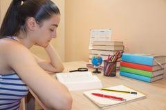 Μελέτη κοριτσιών Στοχαστική συνεδρίαση νέων κοριτσιών στο γραφείο με το βιβλίο Στοκ Φωτογραφία