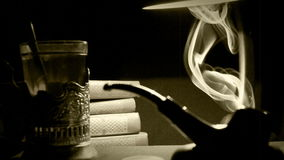 μελέτη του σοβιετικού πληροφοριών της δεκαετίας του '30 ανώτερου υπαλλήλου υπηρεσίας: σωλήνας καπνών, ένας σωρός των βιβλίων και  απόθεμα βίντεο