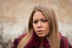 Μελαγχολικό νέο κορίτσι με το κόκκινο παλτό γουνών Στοκ Εικόνες