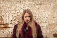 Μελαγχολικό νέο κορίτσι με το κόκκινο παλτό γουνών Στοκ φωτογραφία με δικαίωμα ελεύθερης χρήσης