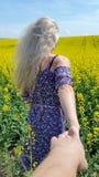 Με ακολουθήστε Ξανθό κορίτσι στο φόρεμα με την τυπωμένη ύλη λουλουδιών στον ανθίζοντας κίτρινο τομέα συναπόσπορων Στοκ εικόνα με δικαίωμα ελεύθερης χρήσης