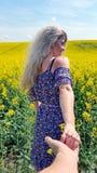 Με ακολουθήστε Ξανθό κορίτσι στο φόρεμα με την τυπωμένη ύλη λουλουδιών στον ανθίζοντας κίτρινο τομέα συναπόσπορων Στοκ Φωτογραφία