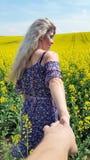 Με ακολουθήστε Ξανθό κορίτσι στο φόρεμα με την τυπωμένη ύλη λουλουδιών στον ανθίζοντας κίτρινο τομέα συναπόσπορων Στοκ Εικόνα