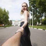 Με ακολουθήστε, η όμορφη νέα γυναίκα κρατά το χέρι ενός άνδρα στοκ εικόνα
