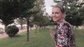 Με ακολουθήστε έννοια κοριτσιών Νέο αρκετά ευτυχές πρότυπο χαμόγελο σπουδαστών και περπάτημα στο πάρκο Αγάπη χεριών ζεύγους φιλμ μικρού μήκους