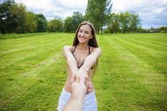 Με ακολουθήστε, η όμορφη νέα γυναίκα κρατά το χέρι ενός άνδρα στοκ εικόνες