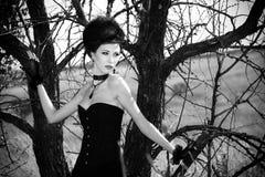 Μελαχροινή βασίλισσα στο πάρκο Μαύρο φόρεμα φαντασίας Στοκ εικόνες με δικαίωμα ελεύθερης χρήσης