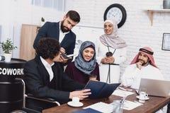 Με ειδικές ανάγκες αραβικό άτομο στην αναπηρική καρέκλα εργασία στην αρχή Το άτομο μοιράζεται τις σημειώσεις με τους συναδέλφους στοκ φωτογραφίες με δικαίωμα ελεύθερης χρήσης