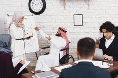 Με ειδικές ανάγκες αραβικό άτομο στην αναπηρική καρέκλα εργασία στην αρχή Το άτομο και ο θηλυκός συνάδελφος κάνουν το presentaion Στοκ φωτογραφία με δικαίωμα ελεύθερης χρήσης