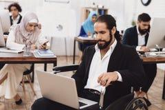 Με ειδικές ανάγκες αραβικό άτομο στην αναπηρική καρέκλα εργασία στην αρχή Το άτομο εργάζεται στο lap-top Στοκ Εικόνα