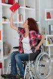 Με ειδικές ανάγκες γυναίκα που αγωνίζεται φθάνοντας στο βιβλίο στο τοπ ράφι στοκ φωτογραφία