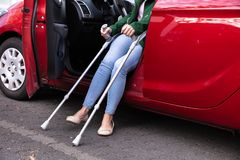 Με ειδικές ανάγκες γυναίκα που βγαίνει από ένα αυτοκίνητο στοκ φωτογραφία με δικαίωμα ελεύθερης χρήσης