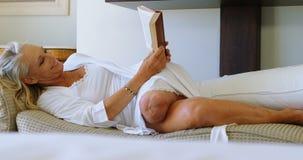 Με ειδικές ανάγκες γυναίκα που διαβάζει ένα βιβλίο στο καθιστικό 4k απόθεμα βίντεο