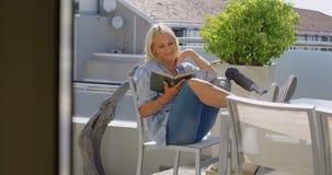 Με ειδικές ανάγκες γυναίκα που διαβάζει ένα βιβλίο στο μπαλκόνι 4k φιλμ μικρού μήκους