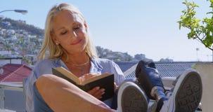 Με ειδικές ανάγκες γυναίκα που διαβάζει ένα βιβλίο στο μπαλκόνι 4k απόθεμα βίντεο