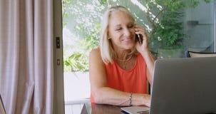 Με ειδικές ανάγκες γυναίκα που μιλά στο κινητό τηλέφωνο χρησιμοποιώντας το lap-top 4k φιλμ μικρού μήκους