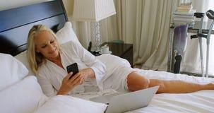 Με ειδικές ανάγκες γυναίκα που χρησιμοποιεί το κινητό τηλέφωνο στην κρεβατοκάμαρα 4k απόθεμα βίντεο