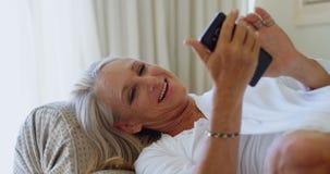 Με ειδικές ανάγκες γυναίκα που χρησιμοποιεί το κινητό τηλέφωνο στο καθιστικό 4k απόθεμα βίντεο