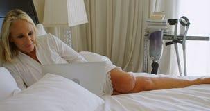Με ειδικές ανάγκες γυναίκα που χρησιμοποιεί το lap-top στην κρεβατοκάμαρα 4k απόθεμα βίντεο