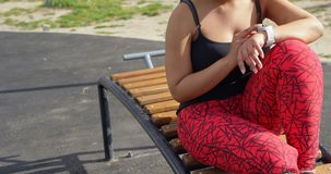 Με ειδικές ανάγκες γυναίκα που χρησιμοποιεί smartwatch στο πάρκο μια ηλιόλουστη ημέρα 4k απόθεμα βίντεο