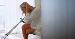Με ειδικές ανάγκες γυναίκα με το δεκανίκι στην κρεβατοκάμαρα στο σπίτι 4k απόθεμα βίντεο