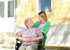 Με ειδικές ανάγκες ηλικιωμένη γυναίκα και νέο caregiver υπαίθρια στοκ εικόνα με δικαίωμα ελεύθερης χρήσης