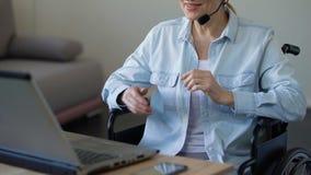Με ειδικές ανάγκες θηλυκός σύμβουλος με την κάσκα που μιλά με τον πελάτη, που εργάζεται στο lap-top φιλμ μικρού μήκους