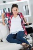 Με ειδικές ανάγκες νέα γυναίκα στην αναπηρική καρέκλα στο σπίτι στο καθιστικό Στοκ Εικόνες