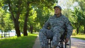Με ειδικές ανάγκες νεαρός άνδρας στη στρατιωτική στολή που κινείται στην αναπηρική καρέκλα στο πάρκο πόλεων, ζημία φιλμ μικρού μήκους