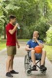 Με ειδικές ανάγκες άτομο μετά από το παιχνίδι καλαθοσφαίρισης με το φίλο Στοκ Εικόνα