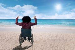 Με ειδικές ανάγκες άτομο σε μια αναπηρική καρέκλα στην παραλία στοκ φωτογραφίες