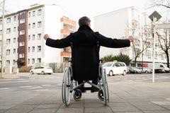 Με ειδικές ανάγκες άτομο στην αναπηρική καρέκλα με το χέρι που αυξάνεται στοκ φωτογραφία με δικαίωμα ελεύθερης χρήσης