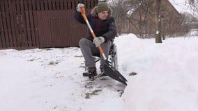 Με ειδικές ανάγκες άτομο στην αναπηρική καρέκλα με το χιόνι showel στο ναυπηγείο απόθεμα βίντεο